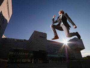 businessman-jumping-and-smiling-outside-office